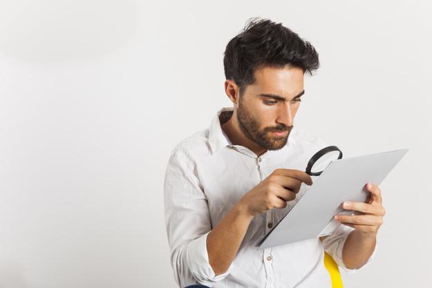 Allegoria attenzione top-down:giovane uomo cerca con lente di ingrandimento su un folgio di carta