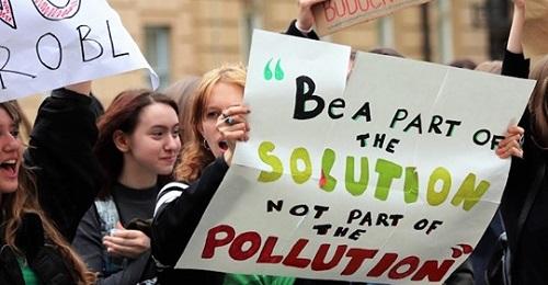 Greta Thunberg in manifestazione, una ragazza a destra tiene un cartello con uno slogan