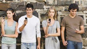 quattro giovani (due maschi e due femmine) appoggiati contro un muro guardano i loro cellulari