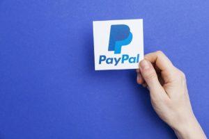 mano che tiene una tessera con logo paypal su sfondo azzurro