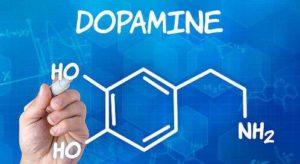 mano che tiene la formula della dopamina su sfondo blu